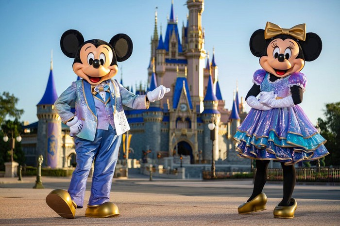 Mickey and Minnie dressed in new duds for the fiftieth anniversary of Disney World. They are in front of the Magic Kingdom's Cinderella Castle.