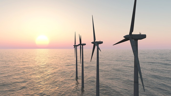 Offshore wind turbines with a setting sun in the background.