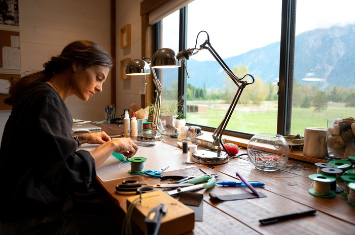 A woman making jewelry.