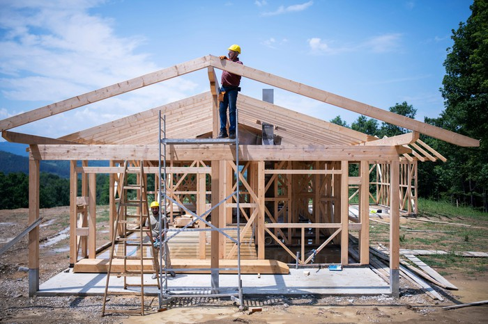 A house frame with a worker nailing in a piece of wood.