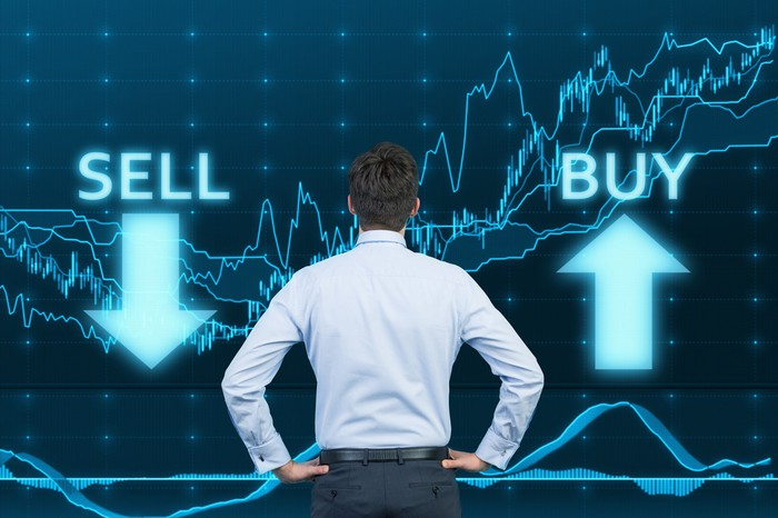 Man with hands on his hips looking at lighted images of sell with a down arrow and buy with an up arrow with stock charts in the background