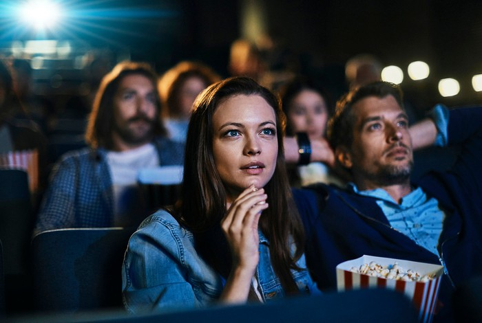 A couple eating popcorn while watching a film inside a crowded movie theater.
