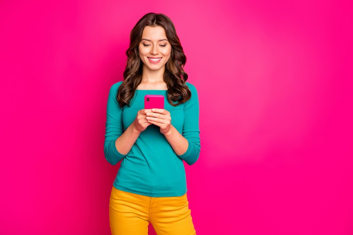 Woman purchasing insurance on Lemonade pink smartphone, standing against pink background.