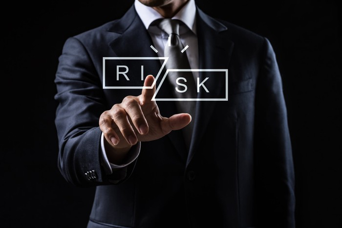 A person in a business suit reaches out and touches the word Risk, which has been cut in two.