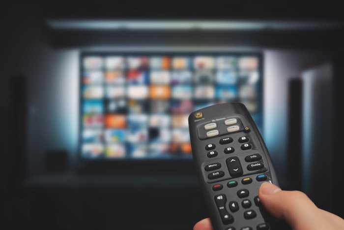 Person holding remote as they choose among streaming options.