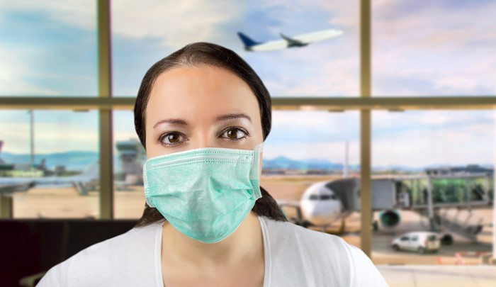 A woman wearing a surgical mask at an airport, with a plane taking off behind her