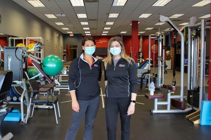 Two workers standing in a room full of exercise equipment.