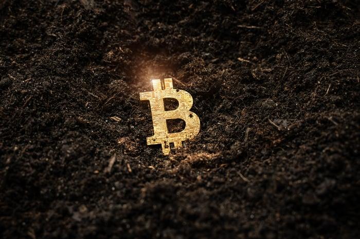 A gold bitcoin emblem in the dirt.