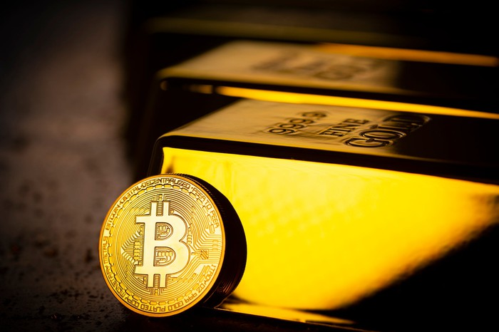 A coin with the Bitcoin logo rests against one of several gold bullions.
