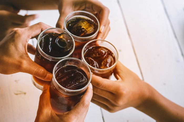 Four hands clinking soda glasses together in a toast