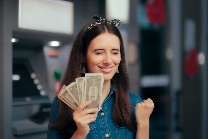 Smiling woman clutching money in front of ATMs.