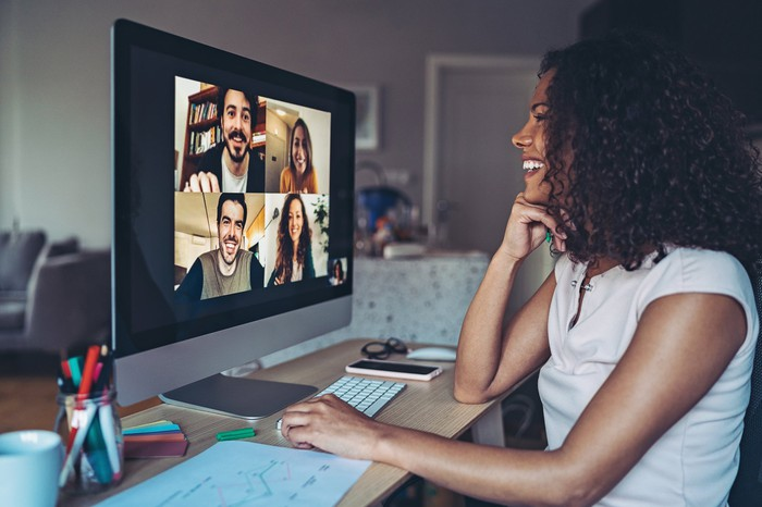 A young woman chats to her friends on a video conferencing platform.