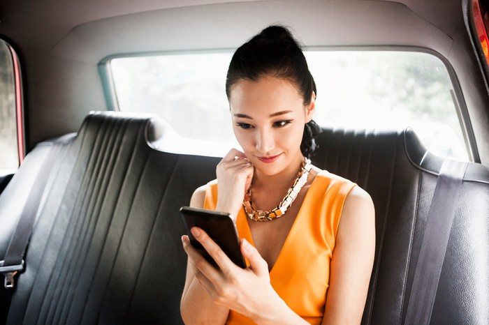 Woman sitting in car looking at smartphone