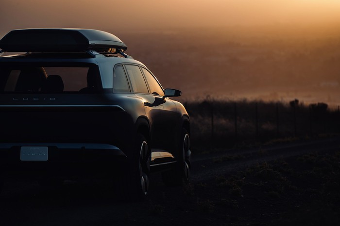 A prototype Lucid SUV, shown in dim light from behind.
