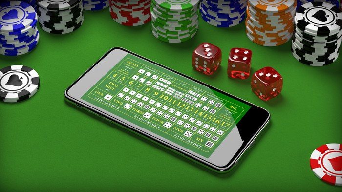 A smartphone with card icons on its screen, on a green baize tabletop surrounded by poker chips and dice.