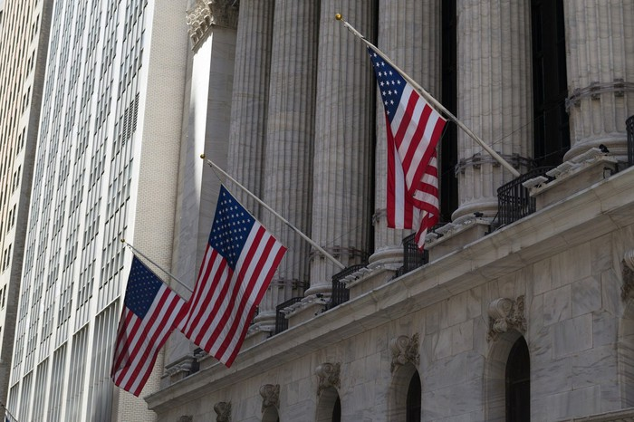 The front of the New York Stock Exchange, with flags hanging from the top of the columns.