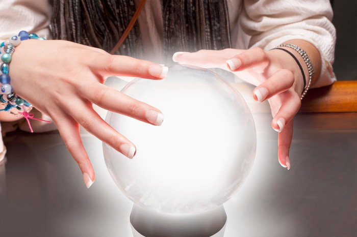 Fortune teller moves hands over a crystal ball