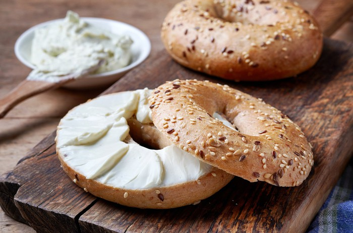 Bagel with cream cheese on a wood cutting board
