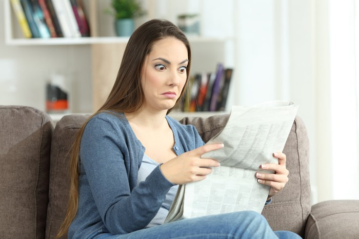 A young woman, reading the newspaper, raises her eyebrows and widens her eyes.