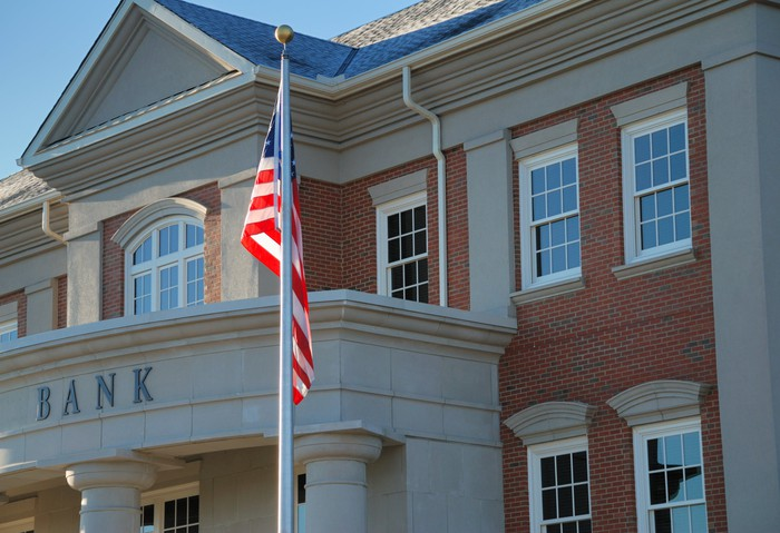 Exterior of a brick bank with an American flag outside.