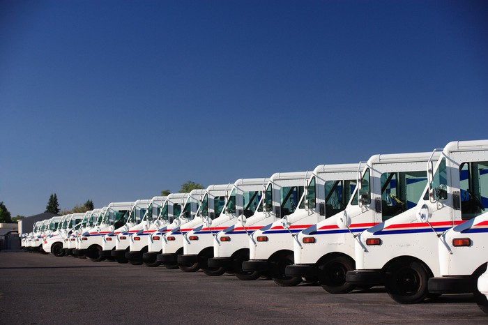 Stock photo of a fleet of U.S. postal service vehicles parked in a line.
