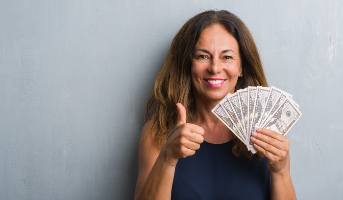 A smiling woman holding hundred dollar bills fanned out is giving a thumbs-up.