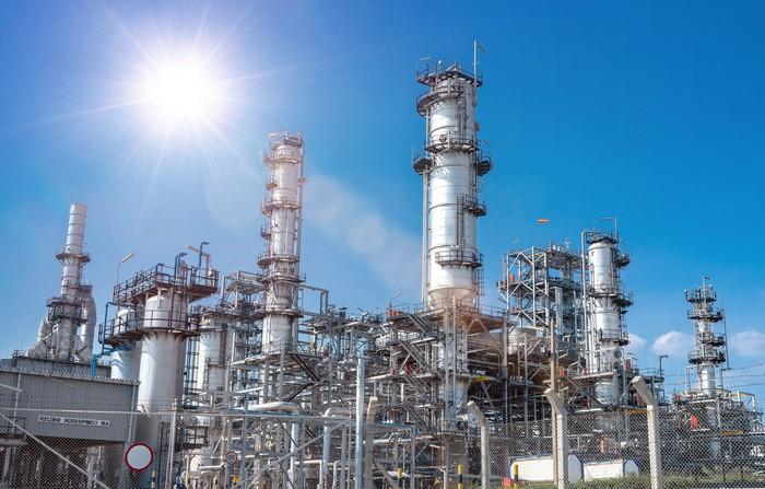 A refinery under a blue cloudless sky and a bright shining sun.