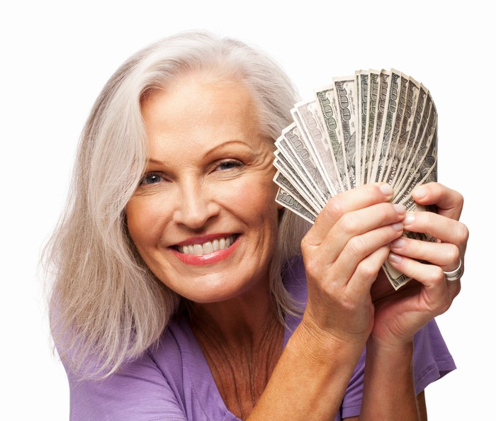 A smiling woman is holding hundred-dollar bills fanned out near her face.