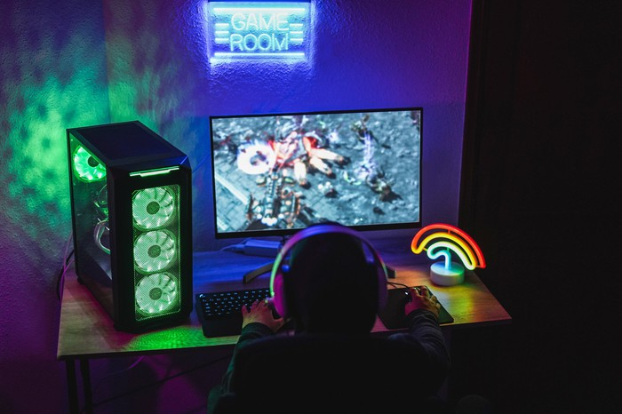 A kid playing a game at a souped-up gaming PC.