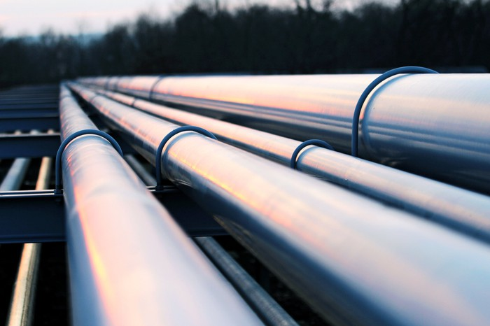 A bunch of silver colored crude oil pipelines.