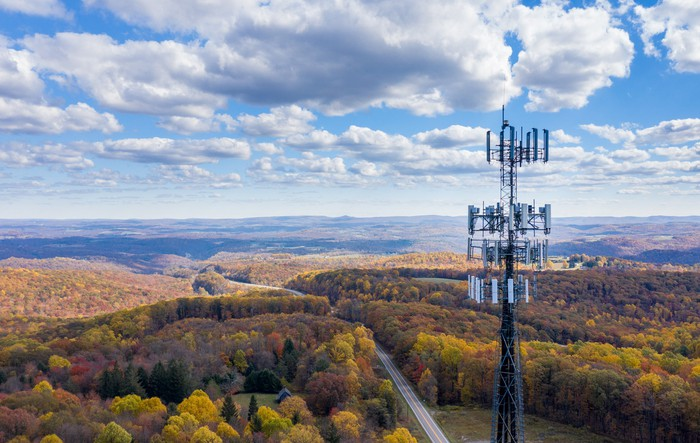 A telecom tower perched above a highway in a hilly, forested, rural area.