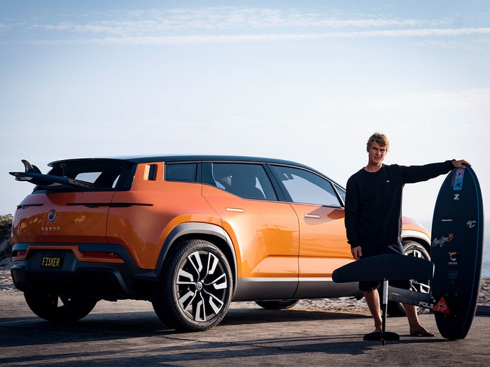 Rear view of orange Fisker Ocean electric SUV with surfer and boards.