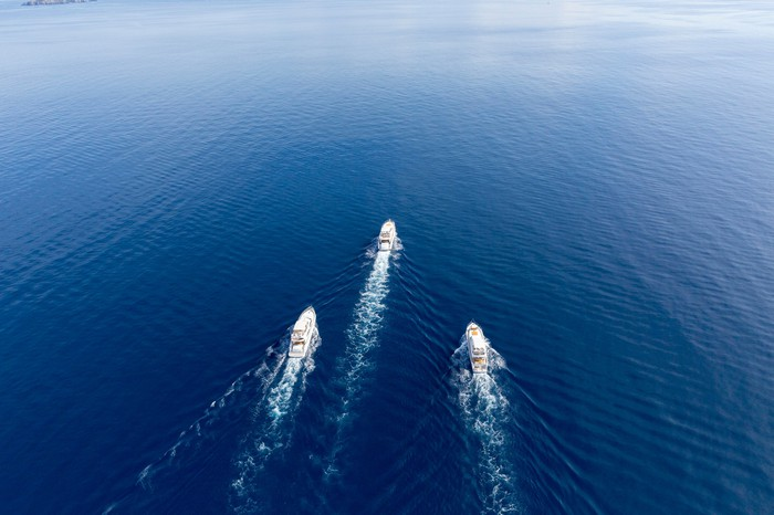 3 ships racing across a blue sea