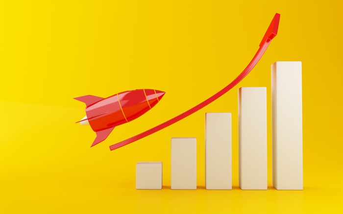 A red rocket ship prepares to fly over a rising bar chart.