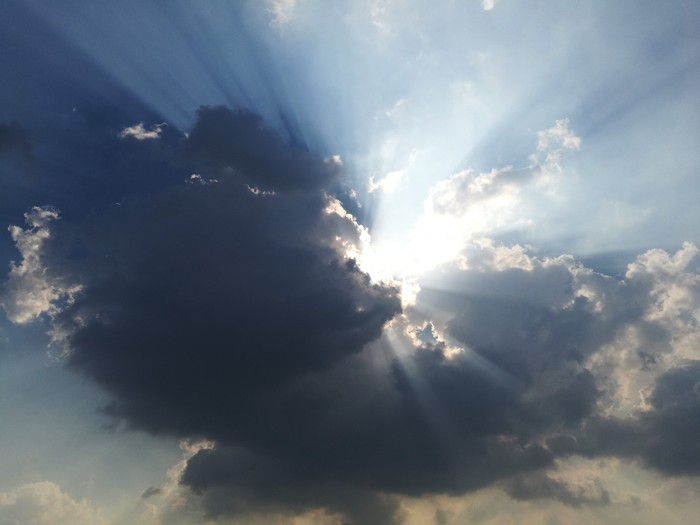 The sun breaking out of dark clouds.