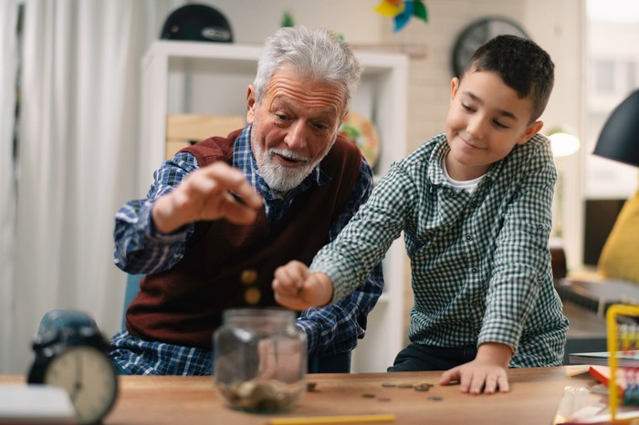 Senior man and young boy putting change in jar