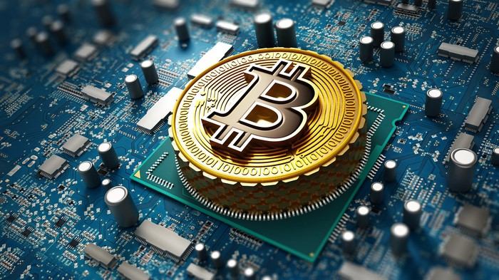 A Bitcoin token sitting on a computer chip.