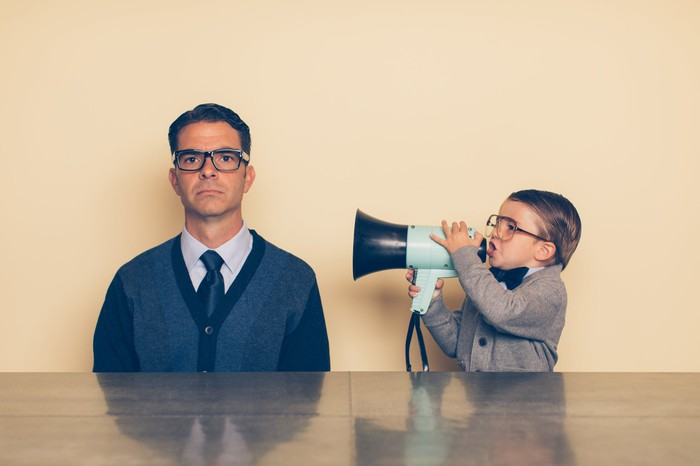 A child uses a megaphone to talk to a man who is sitting, seemingly not paying attention
