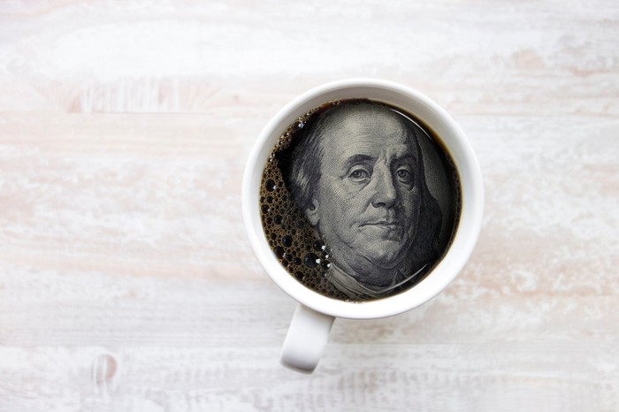 Ben Franklin's face from hundred dollar bill in coffee cup
