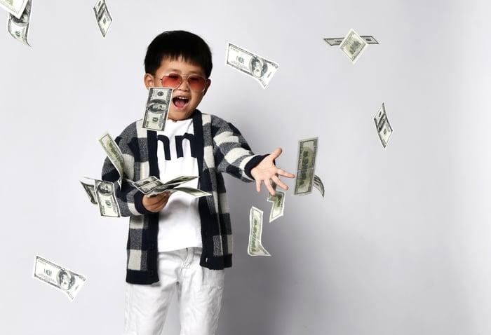 Un enfant qui jette de l'argent.