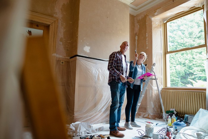 An older couple surveys the construction work in a room