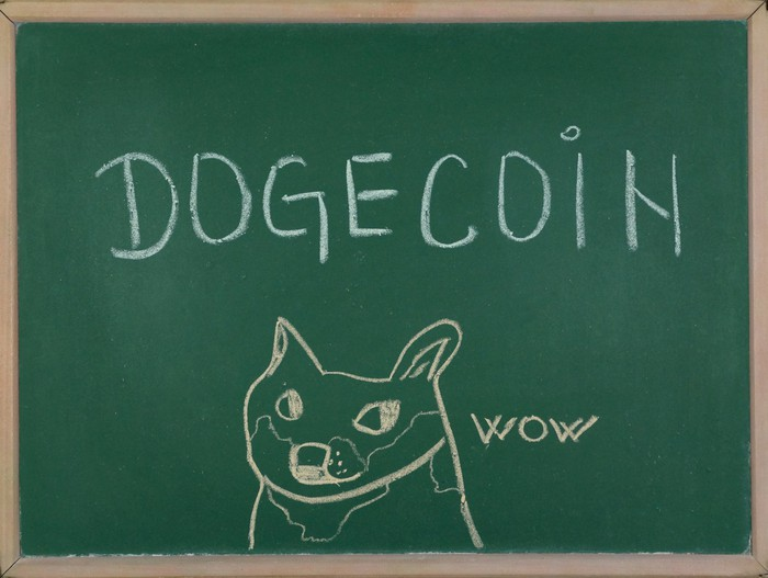 A chalkboard with the word Dogecoin in block letters, next to a crudely drawn dog saying Wow.