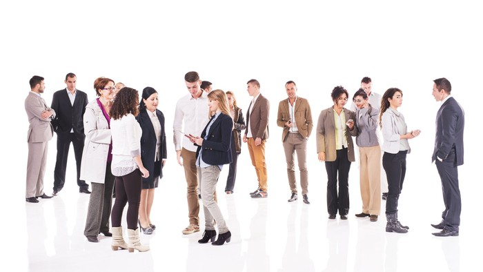 A standing crowd of people talking to one another.