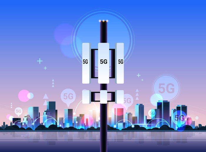 Cartoon of tower with antennas labeled 5G on them in front of a city skyline.