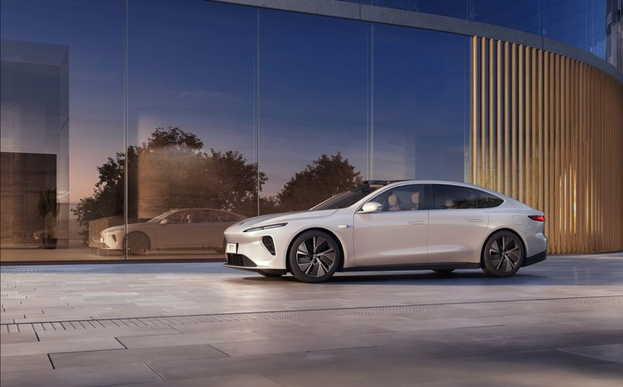 NIO ET7 electric sedan parked beside a reflecting wall.