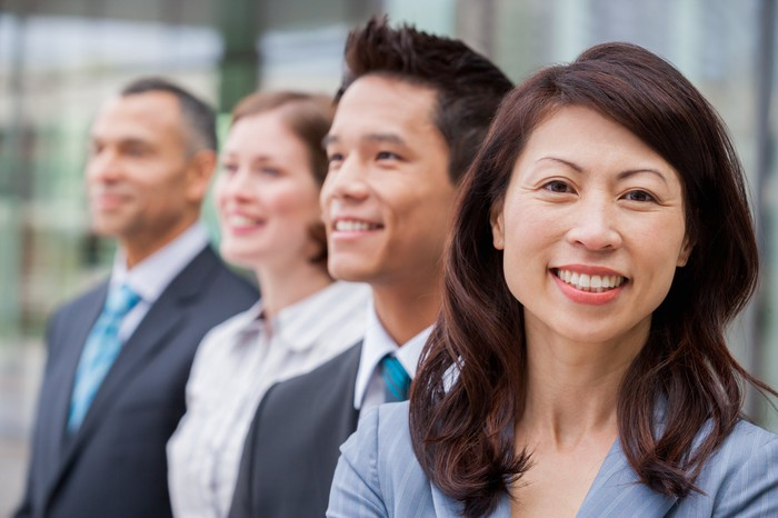 Two men and two women in business clothes, of different races, smiling