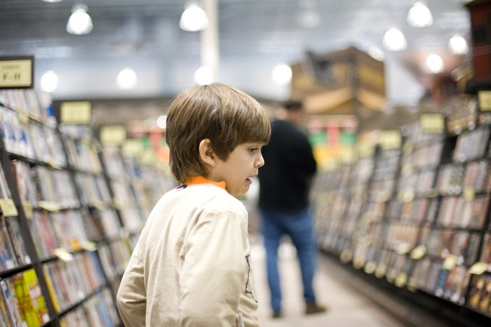 Boy inside a store looking at shelves of video game titles.