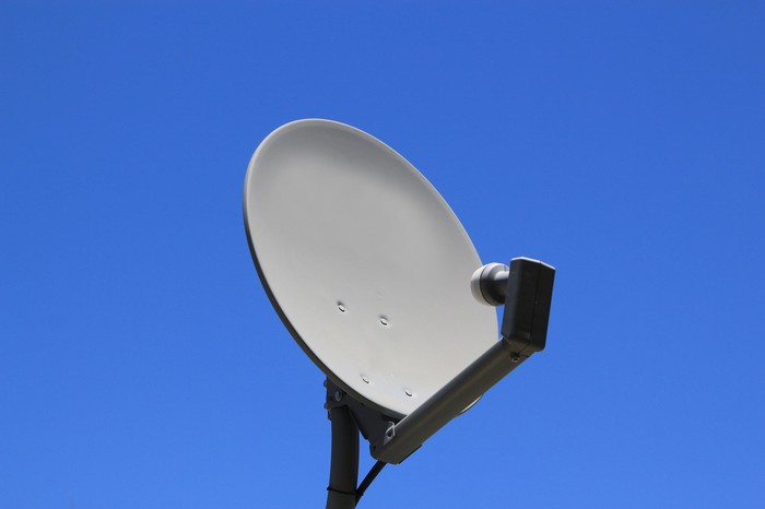 A satellite dish with a blue sky in the background.