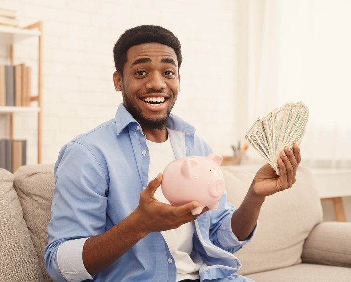Man with cash and a piggy bank.