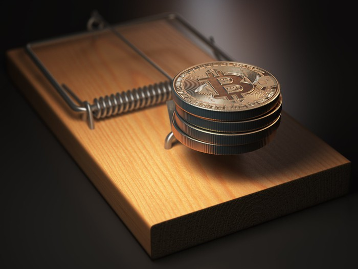 A small stack of physical Bitcoin set as bait in a mouse trap.